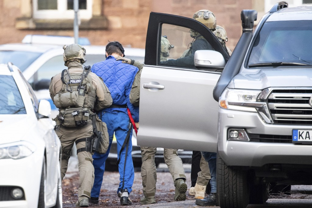 Police officers escort a s suspect after his arrival at the federal prosecutor's office in Karlsruhe Germany, Tuesday, Feb. 11, 2020.  Almost half a y...