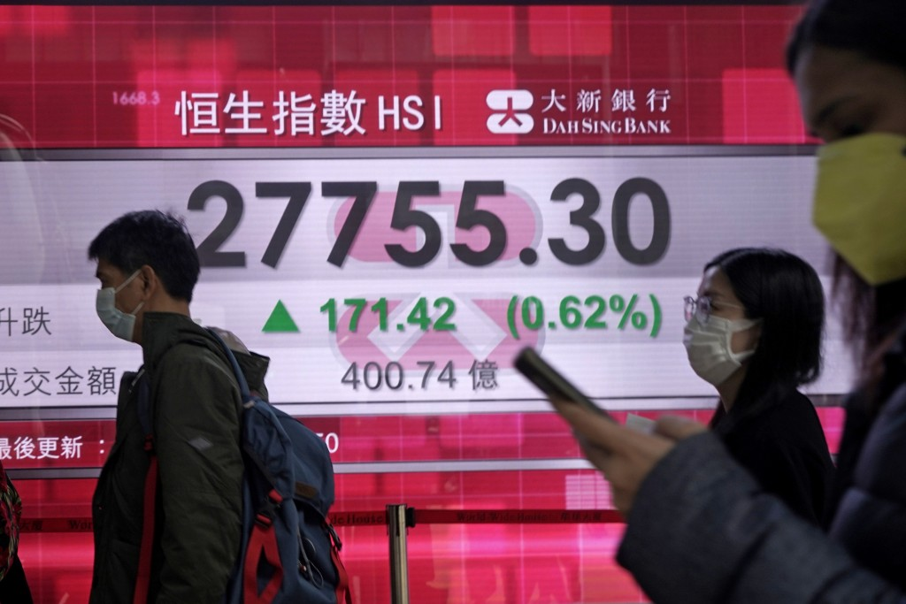 People walk past an electronic board showing Hong Kong share index outside a local bank in Hong Kong, Wednesday, Feb. 12, 2020. Asian shares were high...