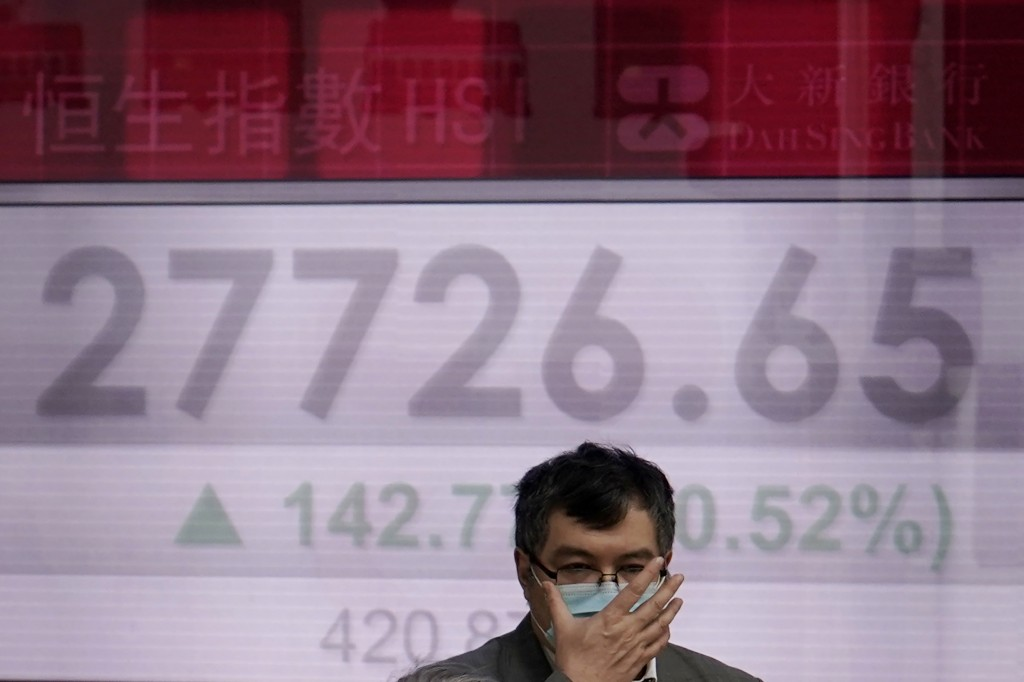 A man walks past an electronic board showing Hong Kong share index outside a local bank in Hong Kong, Wednesday, Feb. 12, 2020. Asian shares were high...