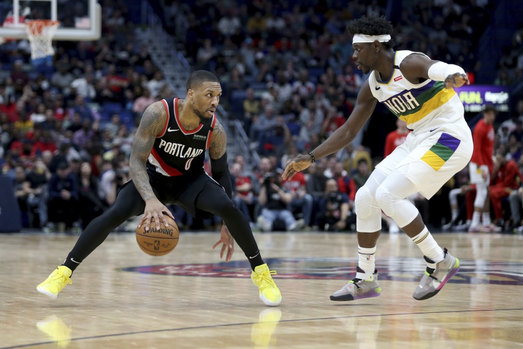 Portland Trail Blazers guard Damian Lillard (0) dribbles the ball as New Orleans Pelicans guard Jrue Holiday (11) defends in the first half of an NBA ...
