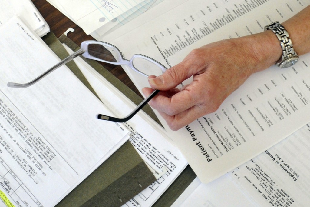 FILE - In this Dec. 20, 2011 file photo, medical bills and other records are spread out on the kitchen table of a patient in Salem, Va. According to a...