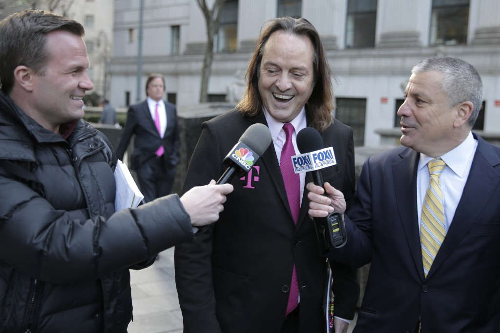 FILE - In this Jan. 15, 2020, file photo T-Mobile chief executive John Legere speaks to reporters as he leaves the courthouse in New York. A federal j...