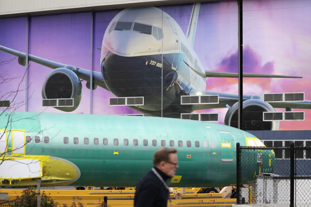 FILE - In this Dec. 16, 2019, file photo a Boeing worker walks past a 737 model fuselage and a giant mural of a jet on the side of the manufacturing b...
