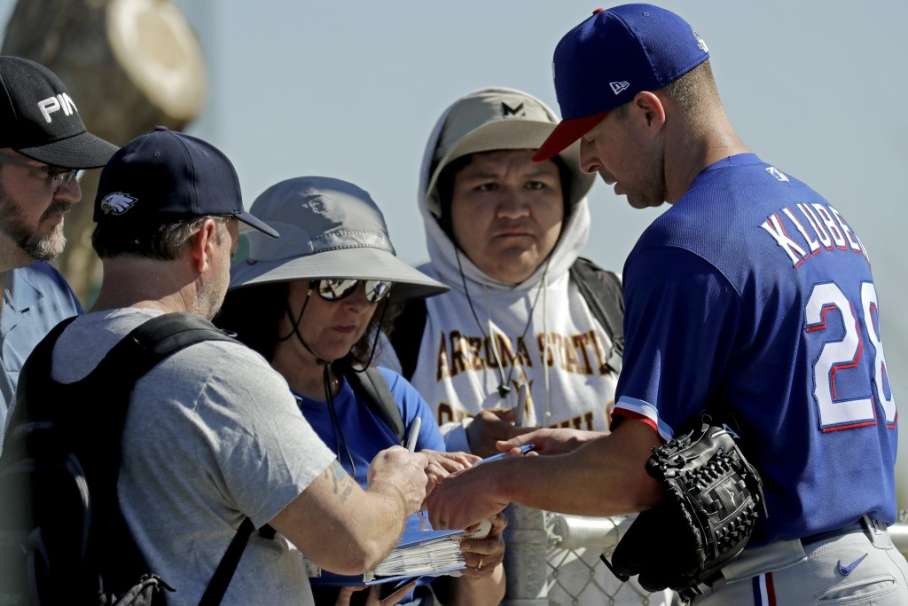 Texas Rangers pitcher Corey Kluber, right, gives autographs during spring training baseball practice Friday, Feb. 14, 2020, in Surprise, Ariz. (AP Pho...