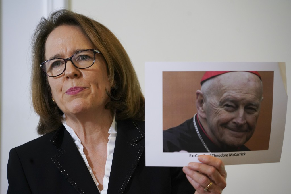 Anne Barrett Doyle, co-director of BishopAccountability.org, holds a photo of ex Cardinal Theodore McCarrick as she talks to the media during a press ...