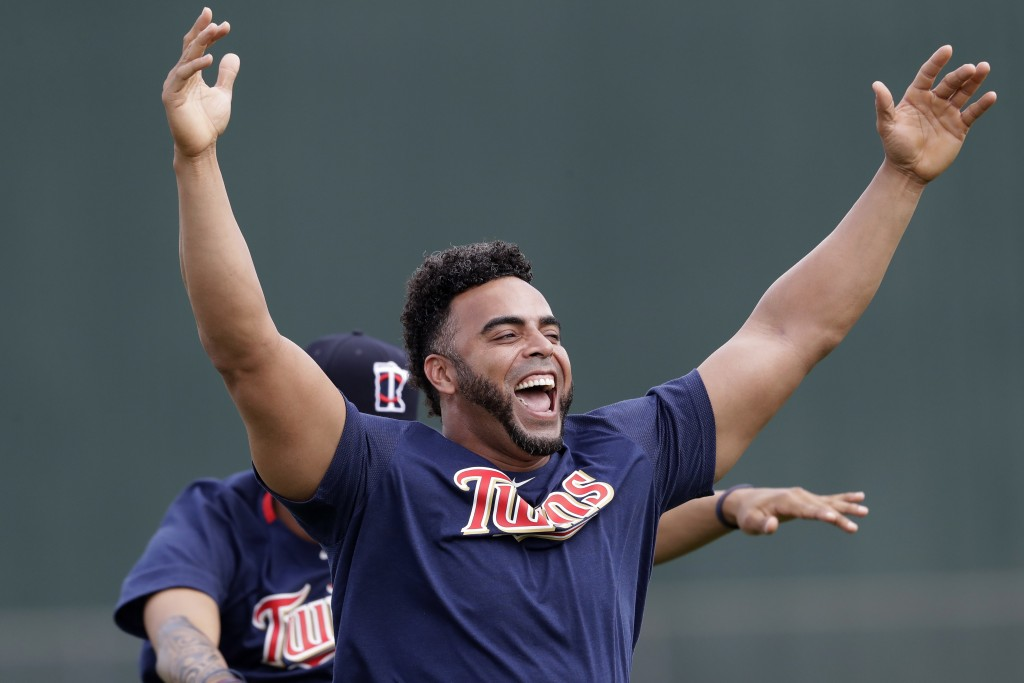 Minnesota Twins designated hitter Nelson Cruz (23) laughs with his teammates as they stretch during spring training baseball camp Sunday, Feb. 16, 202...