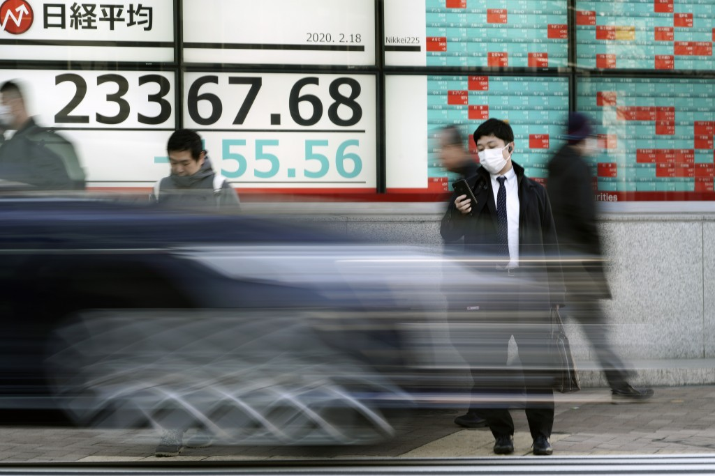 People walk past an electronic stock board showing Japan's Nikkei 225 index at a securities firm in Tokyo Tuesday, Feb. 18, 2020. Shares have fallen i...