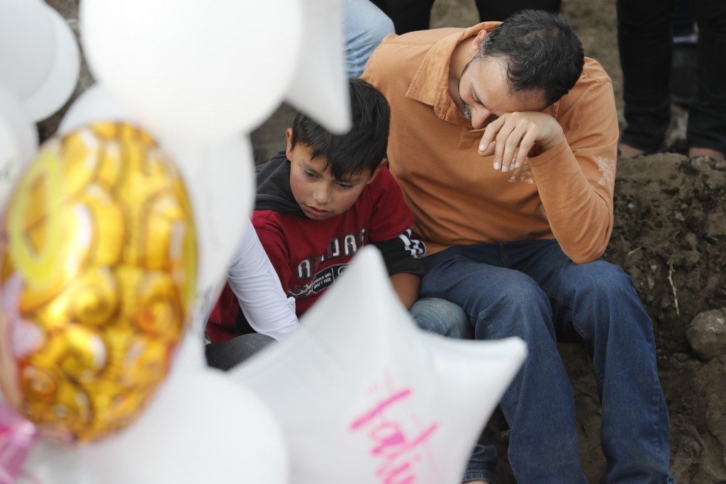 Family members mourn next to the grave of 7-year-old murder victim Fatima in Mexico City, Tuesday, Feb. 18, 2020. Fatima's body was found wrapped in a...
