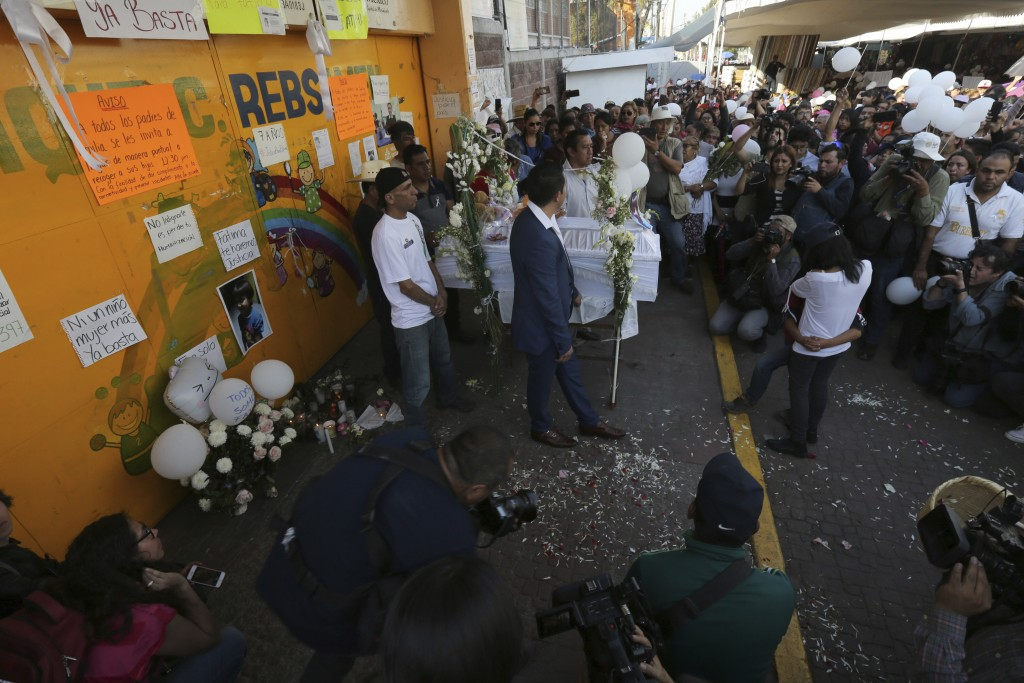 The casket of 7-year-old murder victim Fatima is placed at the gate of the primary school from where she was abducted, as her funeral procession walks...