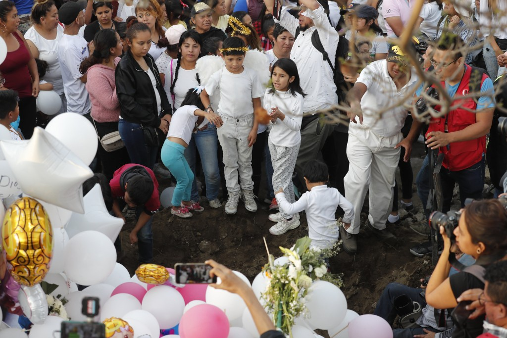 Children sing next to the grave of 7-year-old murder victim Fatima in Mexico City, Tuesday, Feb. 18, 2020. Fatima's body was found wrapped in a bag an...