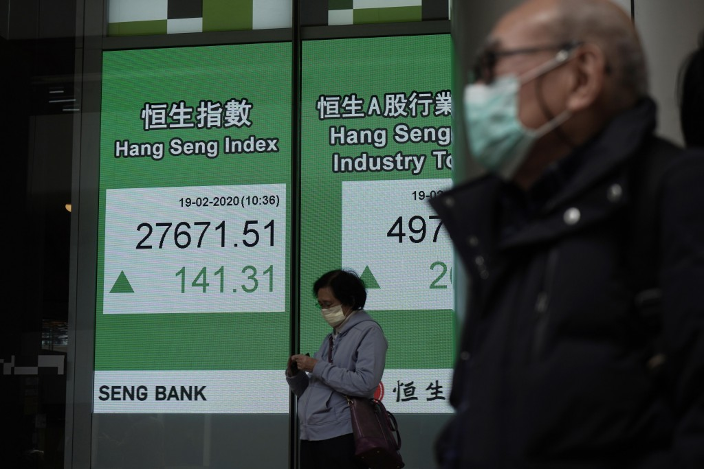 People walk past an electronic board showing Hong Kong share index outside a local bank in Hong Kong, Wednesday, Feb. 19, 2020. Asian shares are mostl...