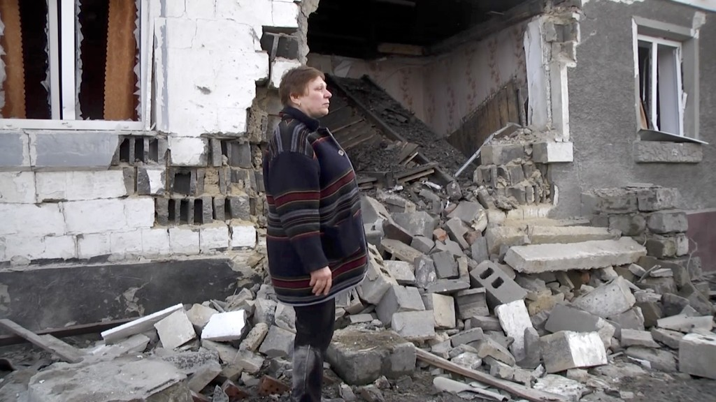 In this video grab provided by the RU-RTR Russian television, a woman stands next to her home, that was distroyed during cross fire between Russia-bac...