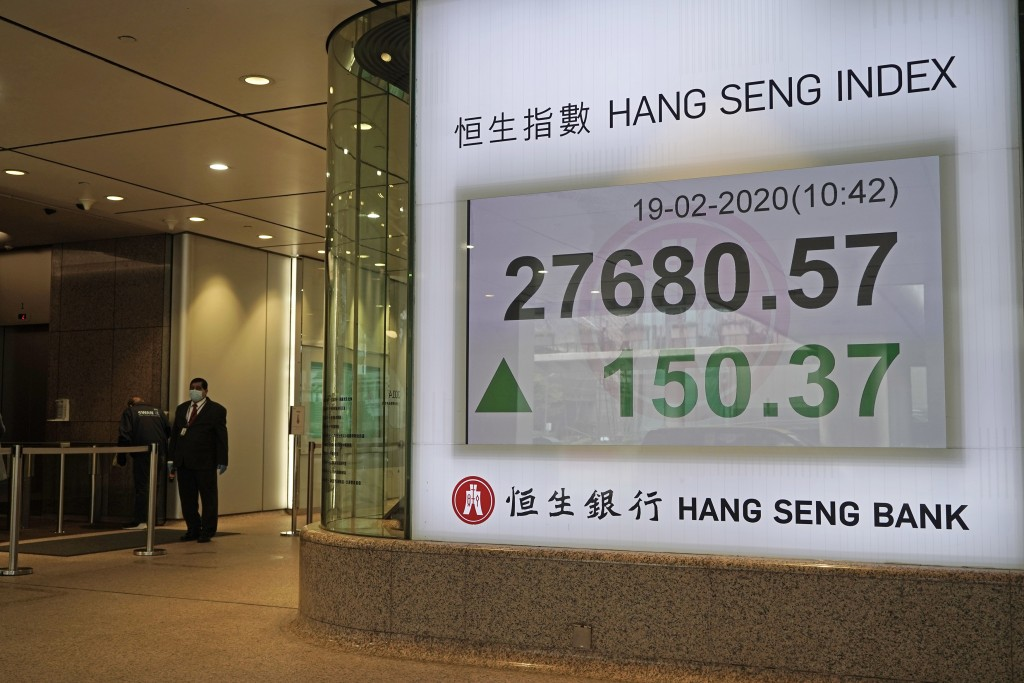 A staff member stands beside an electronic board showing Hong Kong share index outside a local bank in Hong Kong, Wednesday, Feb. 19, 2020. Asian shar...