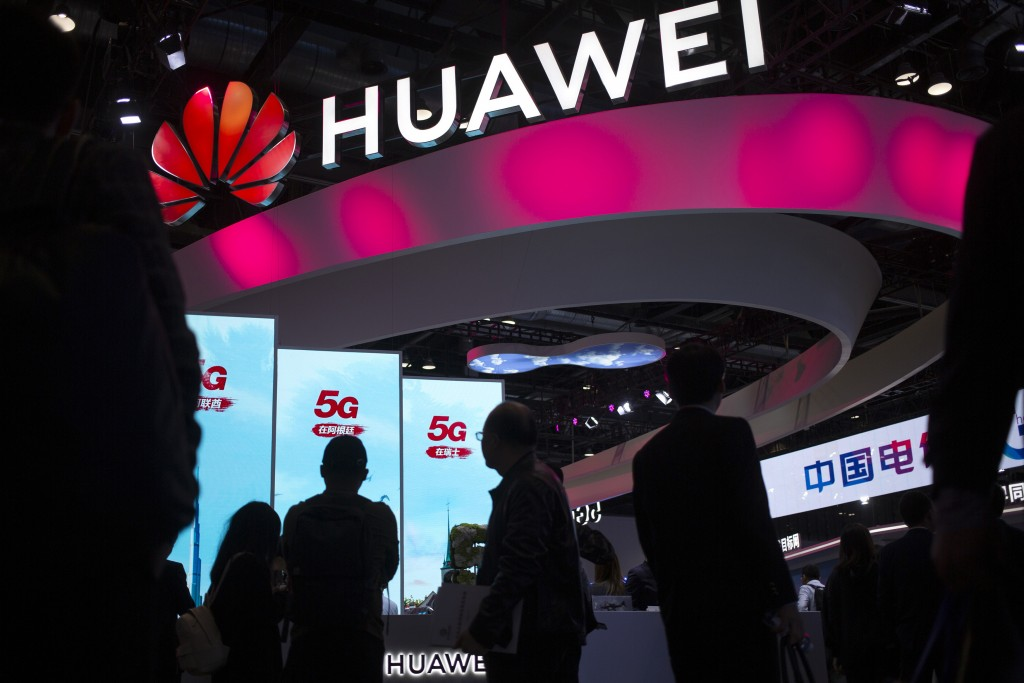 FILE - In this Oct. 31, 2019, file photo, attendees walk past a display for 5G services from Chinese technology firm Huawei at the PT Expo in Beijing....