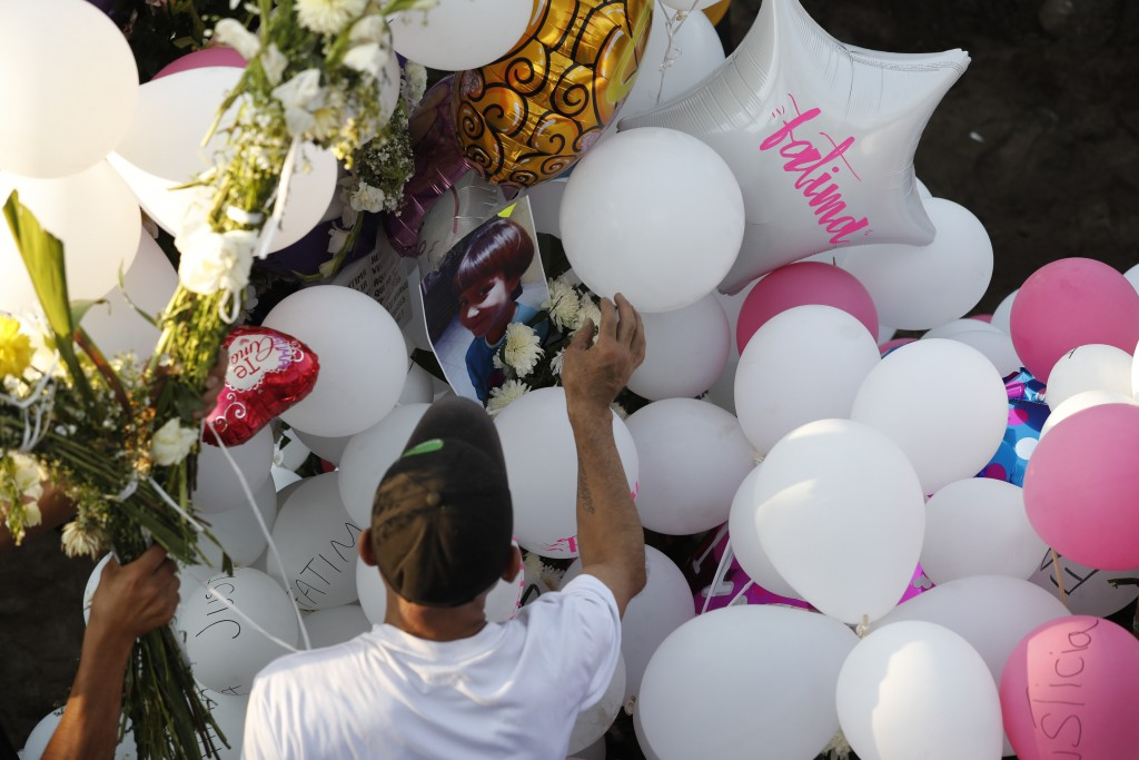 Family members place balloons and flower arrangements on the grave of 7-year-old murder victim Fatima in Mexico City, Tuesday, Feb. 18, 2020. Fatima's...
