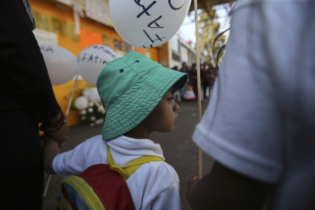 A child, student of the Enrique C. Rebsamen primary school, walks in the funeral procession of 7-year-old murder victim Fatima, accompanied by his par...