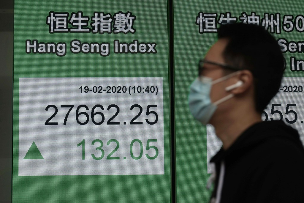 A man walks past an electronic board showing Hong Kong share index outside a local bank in Hong Kong, Wednesday, Feb. 19, 2020. Asian shares are mostl...