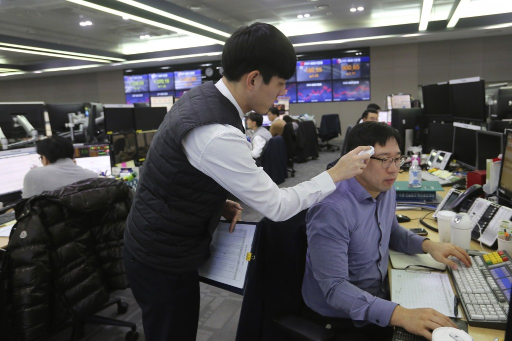 A currency trader checks the temperature of his colleague at the foreign exchange dealing room of the KEB Hana Bank headquarters in Seoul, South Korea...