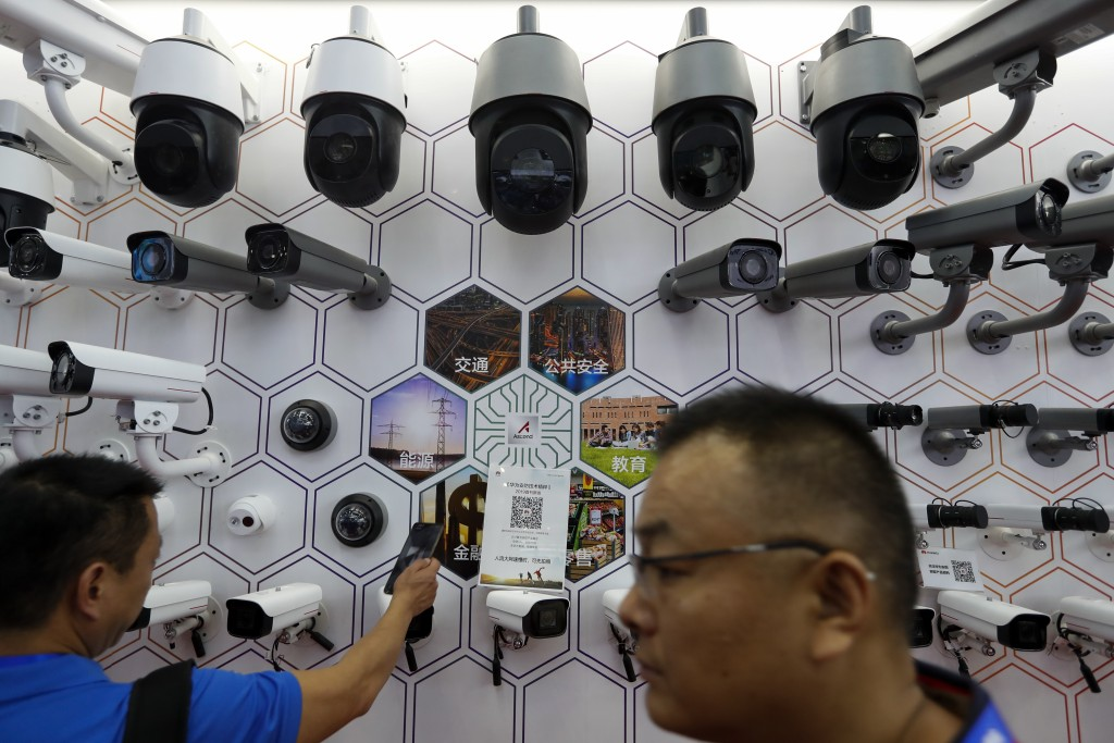 FILE - In this Oct. 29, 2019, file photo visitors look at the surveillance cameras by China's telecoms equipment giant Huawei on display at the China ...