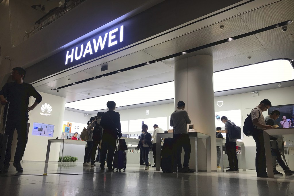 FILE - In this Nov. 15, 2019, file photo people look at a Huawei store in Shenzhen Bao'an International Airport in Shenzhen in southern China's Guangd...