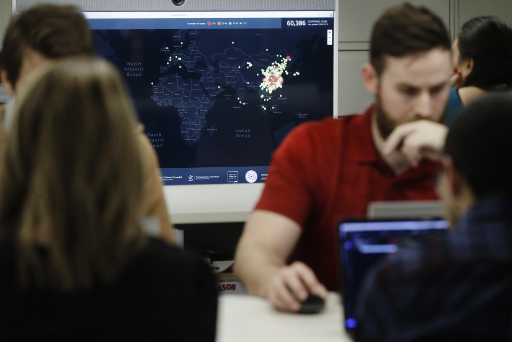 In this Thursday, Feb. 13, 2020 photo, Kyle Martin, a worker at HealthMap, a system using artificial intelligence to monitor global disease outbreaks,...