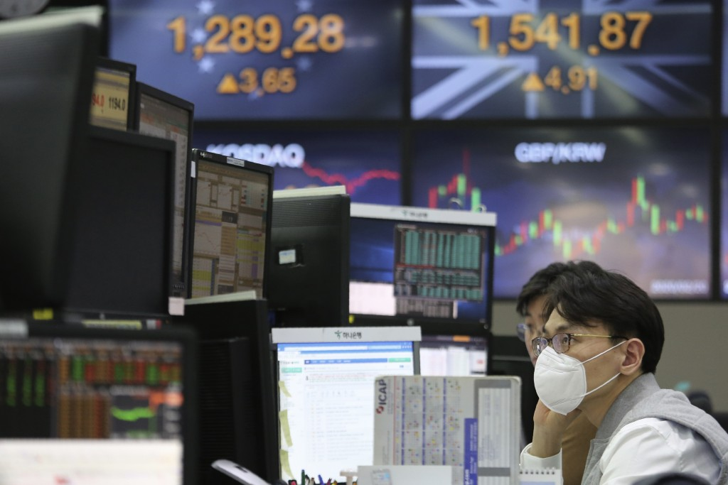 A currency trader wearing a face mask watches monitors at the foreign exchange dealing room of the KEB Hana Bank headquarters in Seoul, South Korea, T...
