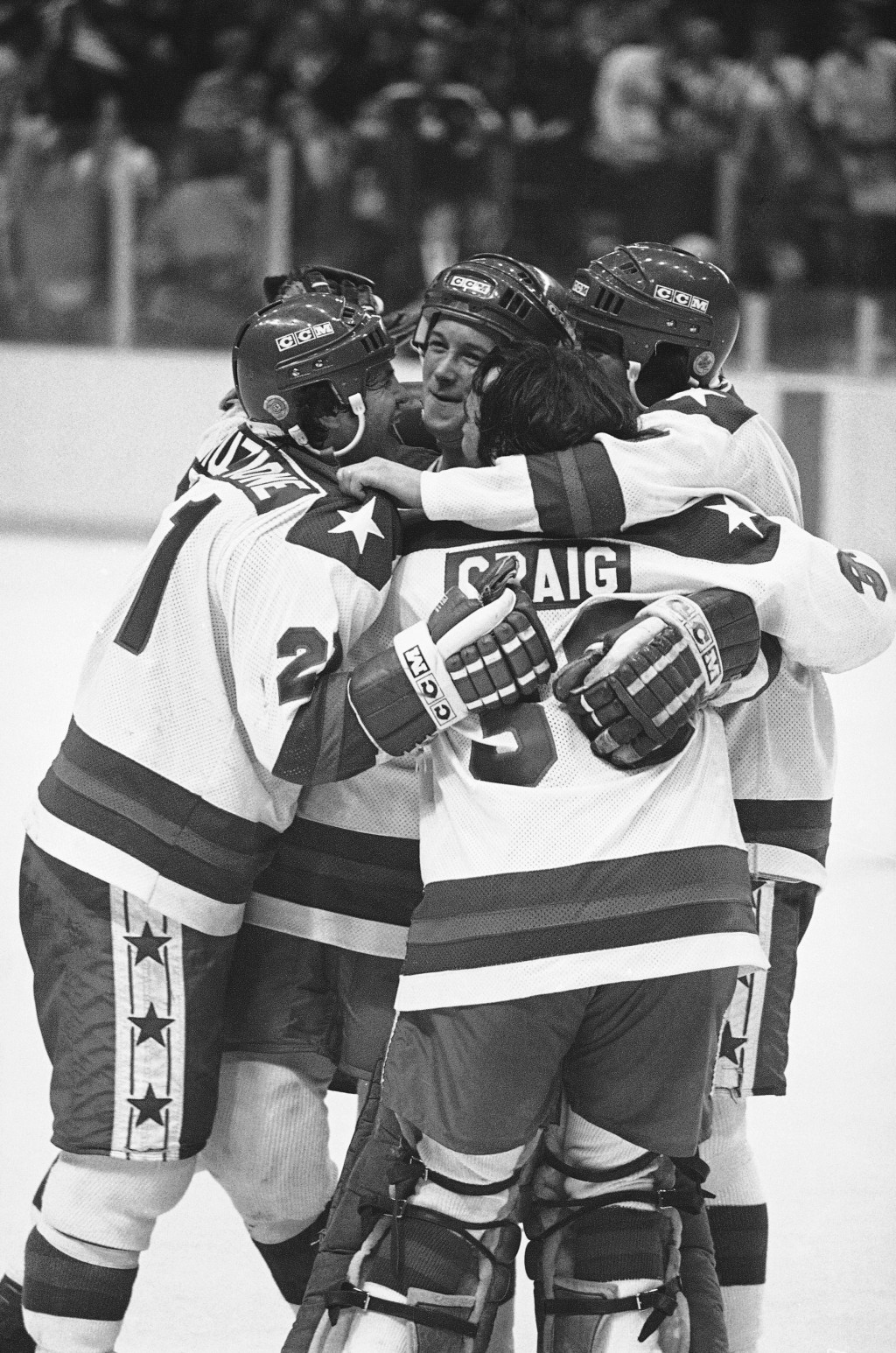 FILE - In this Feb. 22, 1980, file photo, U.S. player Michael Eruzione, left, is congratulated by teammates James Craig, John O'Callahan and David Sil...