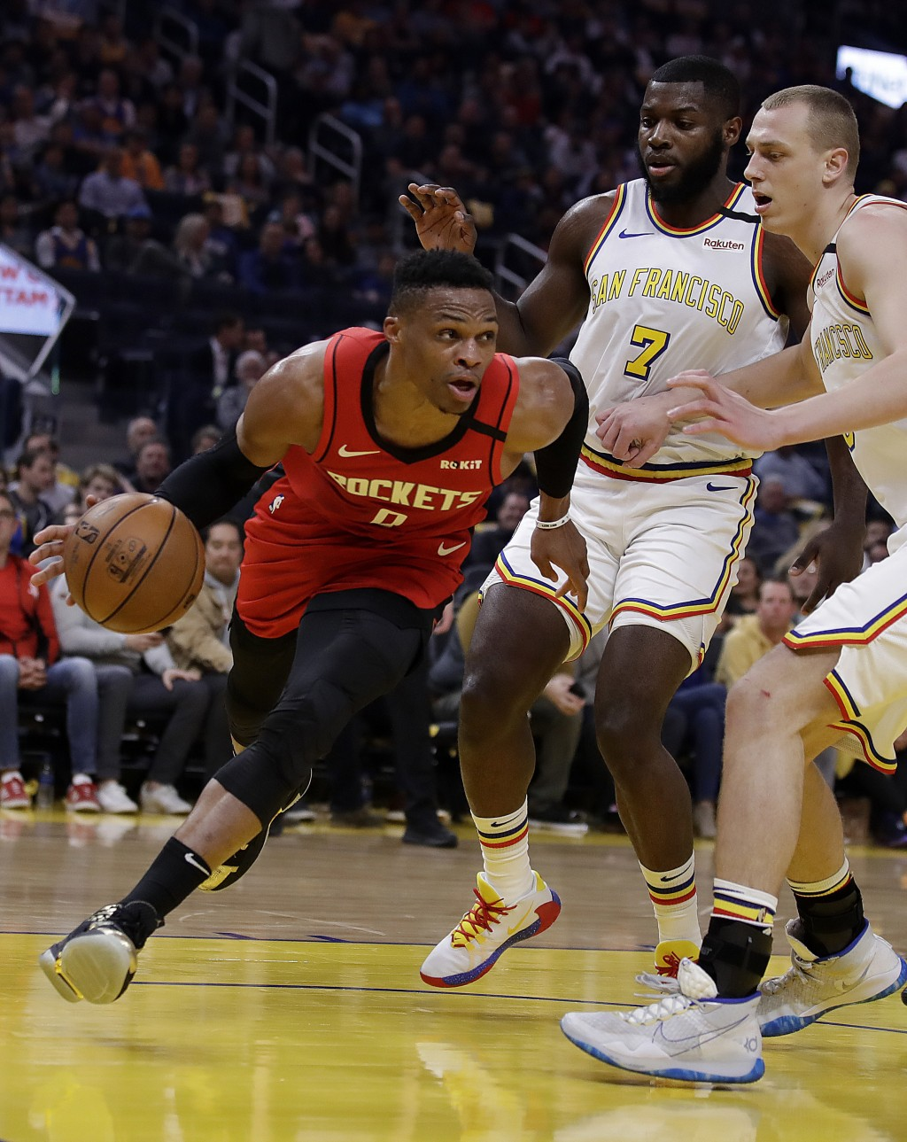 Houston Rockets' Russell Westbrook, left, drives the ball against Golden State Warriors' Eric Paschall (7) and Alen Smailagic, right, during the first...