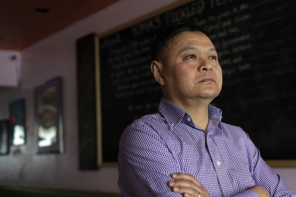In this Thursday, Feb. 13, 2020, photo, Sai Kyaw, an immigrant from Myanmar, also known as Burma, stands for a photograph in Boston at his restaurant ...