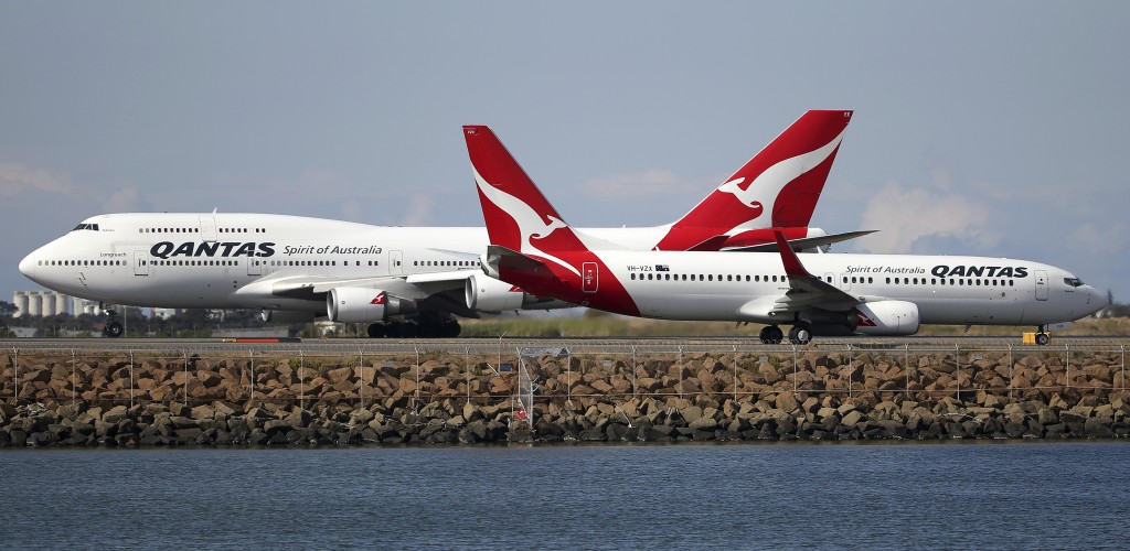 FILE - In this Aug. 20, 2015, file photo, two Qantas planes taxi on the runway at Sydney Airport in Sydney, Australia. The outbreak of the new virus t...
