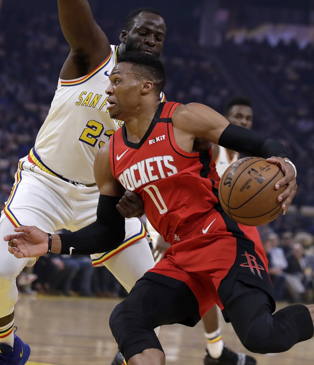 Houston Rockets' Russell Westbrook (0) drives the ball against Golden State Warriors' Draymond Green, left, during the first half of an NBA basketball...