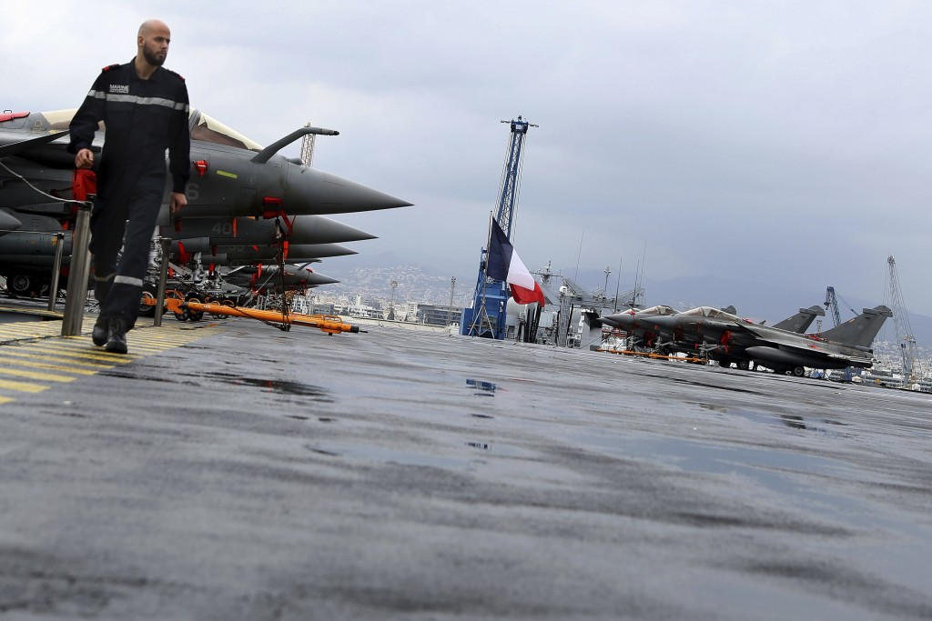 A French sailor walks alongside Rafale warplanes on the deck of the aircraft carrier Charles de Gaulle, docked at Cyprus' main port of Limassol, on Fr...