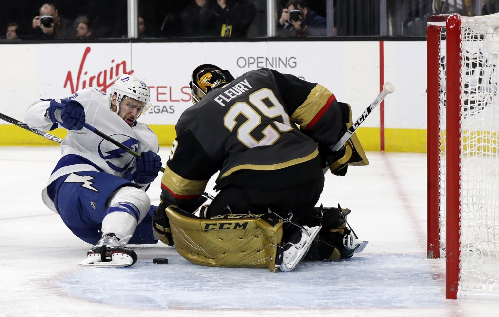 Tampa Bay Lightning forward Cedric Paquette shoots as Vegas Golden Knights goalie Marc-Andre Fleury defends during the third period of an NHL hockey g...