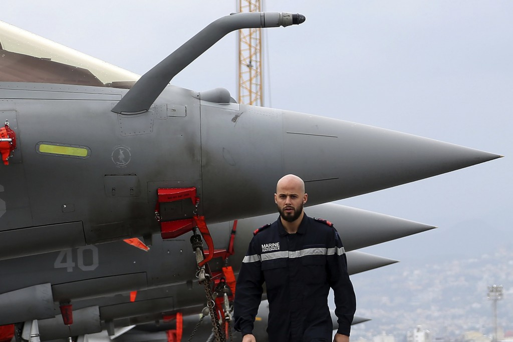 A French sailor walks alongaide Rafale warplanes on the deck of the aircraft carrier Charles de Gaulle, docked at Cyprus' main port of Limassol, on Fr...