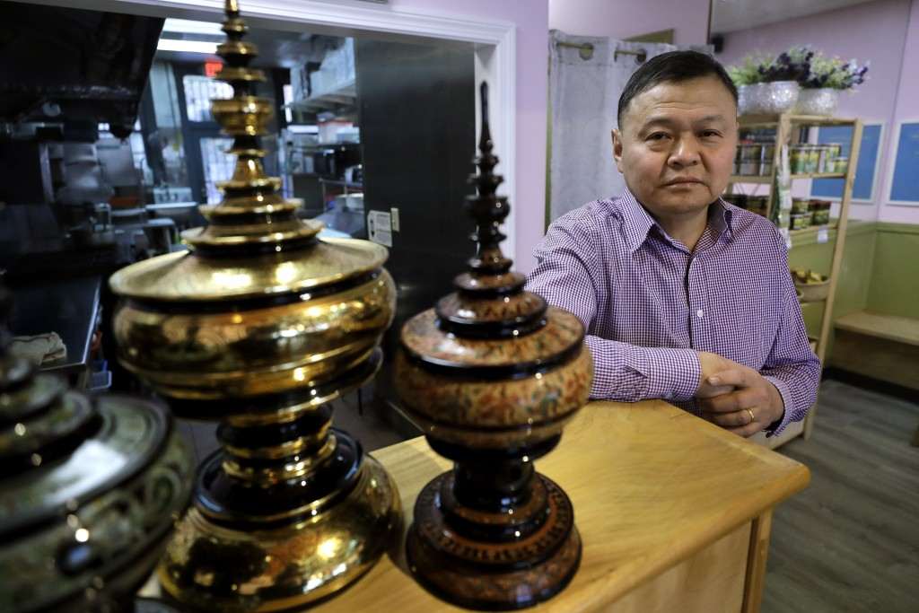In this Thursday, Feb. 13, 2020, photo, Sai Kyaw, an immigrant from Myanmar, also known as Burma, stands for a photograph near traditional Burmese rel...