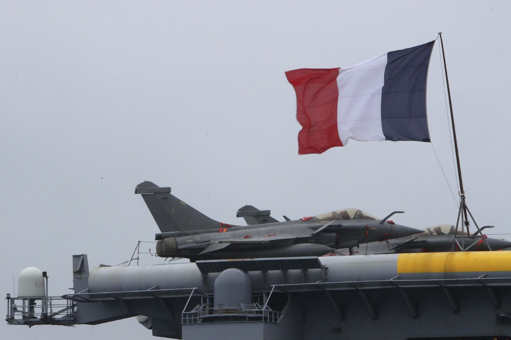 A French flag flies near Rafale warplanes on the deck of the aircraft carrier Charles de Gaulle, docked at Cyprus' main port of Limassol, Friday, Feb....