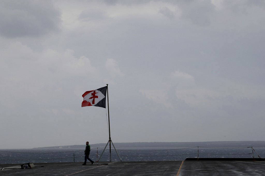 A French sailor walks on the deck of the aircraft carrier Charles de Gaulle, docked at Cyprus' main port of Limassol, on Friday, Feb. 21, 2020. Rear A...
