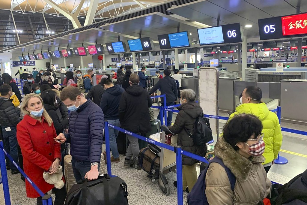 FILE - In this Jan. 30, 2020, file photo, travelers wearing face masks stand in line at the check-in counters for Cathay Pacific at Shanghai Pudong In...