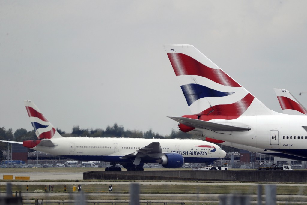 FILE - In this Sept. 9, 2019, file photo, a British Airways plane, left, is towed past other planes sitting parked at Heathrow Airport in London. The ...