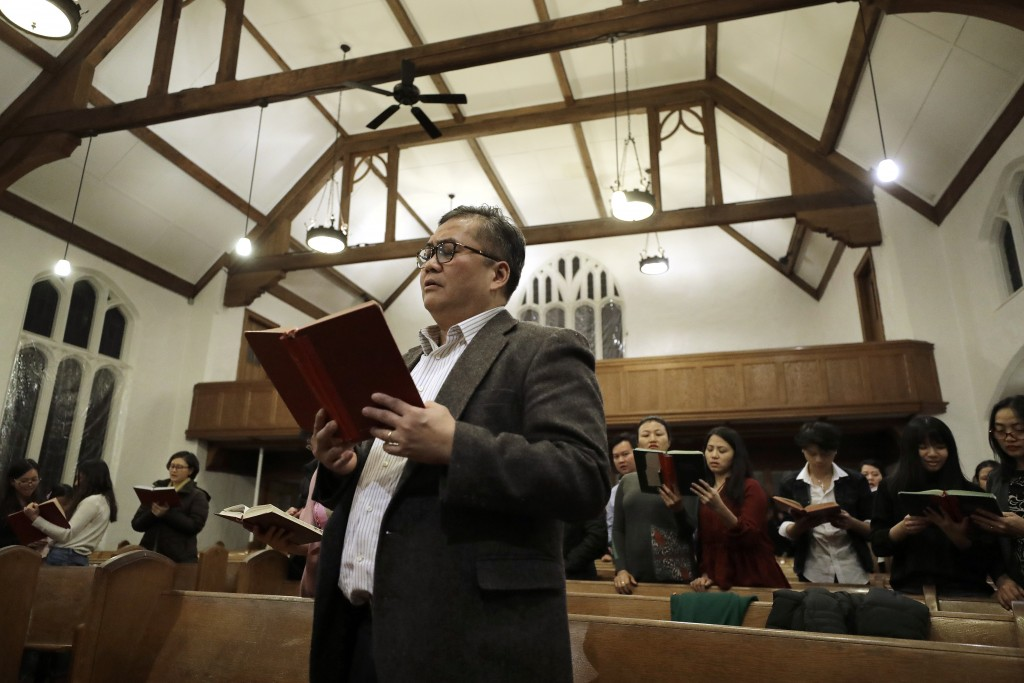 In this Sunday, Feb. 16, 2020, photo Baptist Pastor Clifford Maung, front, an immigrant from Myanmar, also known as Burma, sings a hymn with members o...