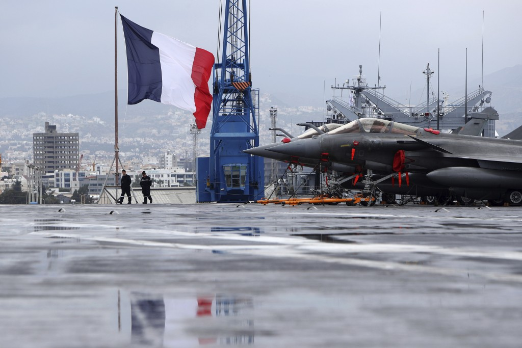 French sailors walk alongside Rafale warplanes on the deck of the aircraft carrier Charles de Gaulle, docked at Cyprus' main port of Limassol, on Frid...