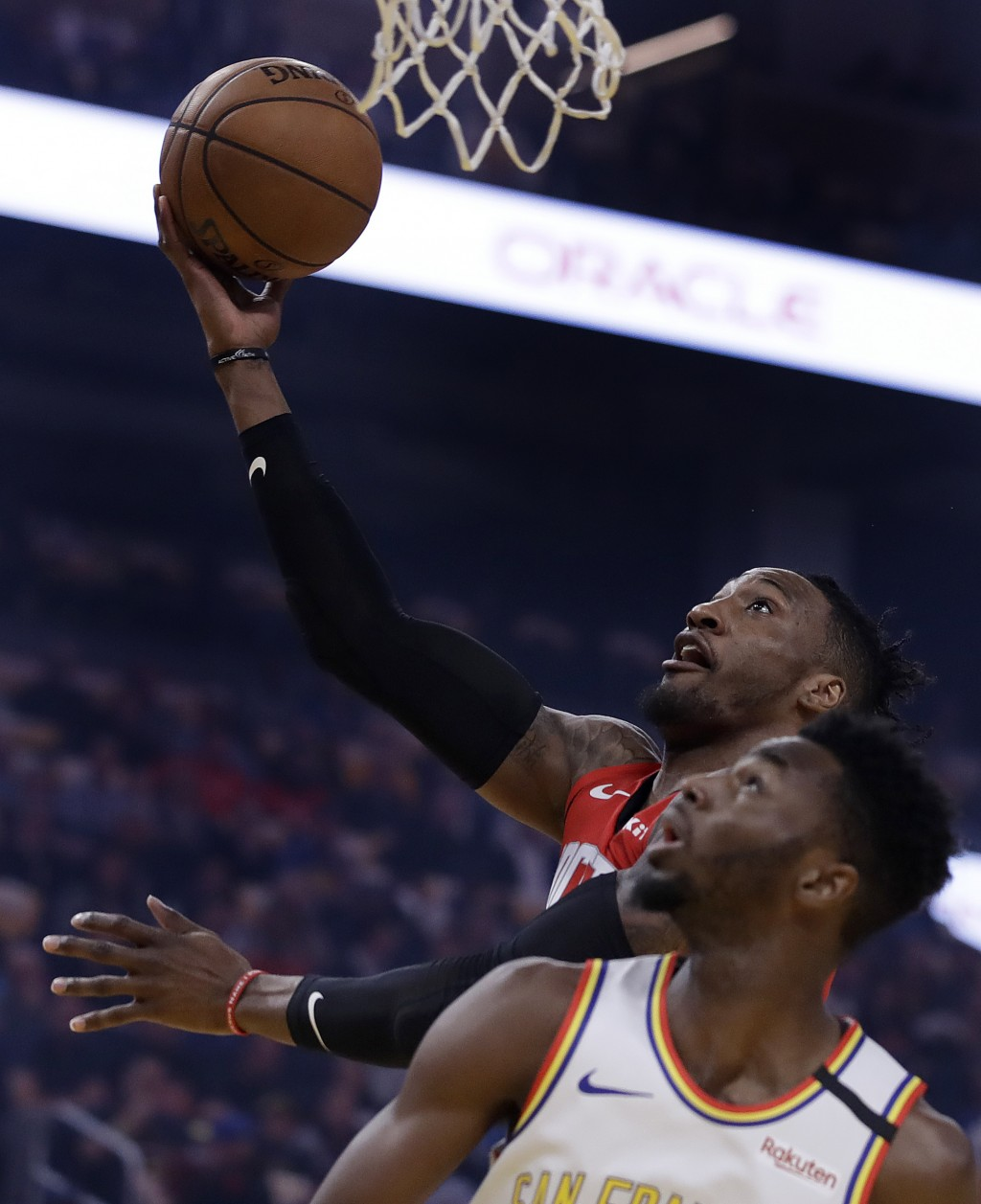 Houston Rockets' Robert Covington lays up a shot over Golden State Warriors' Andrew Wiggins during the first half of an NBA basketball game Thursday, ...