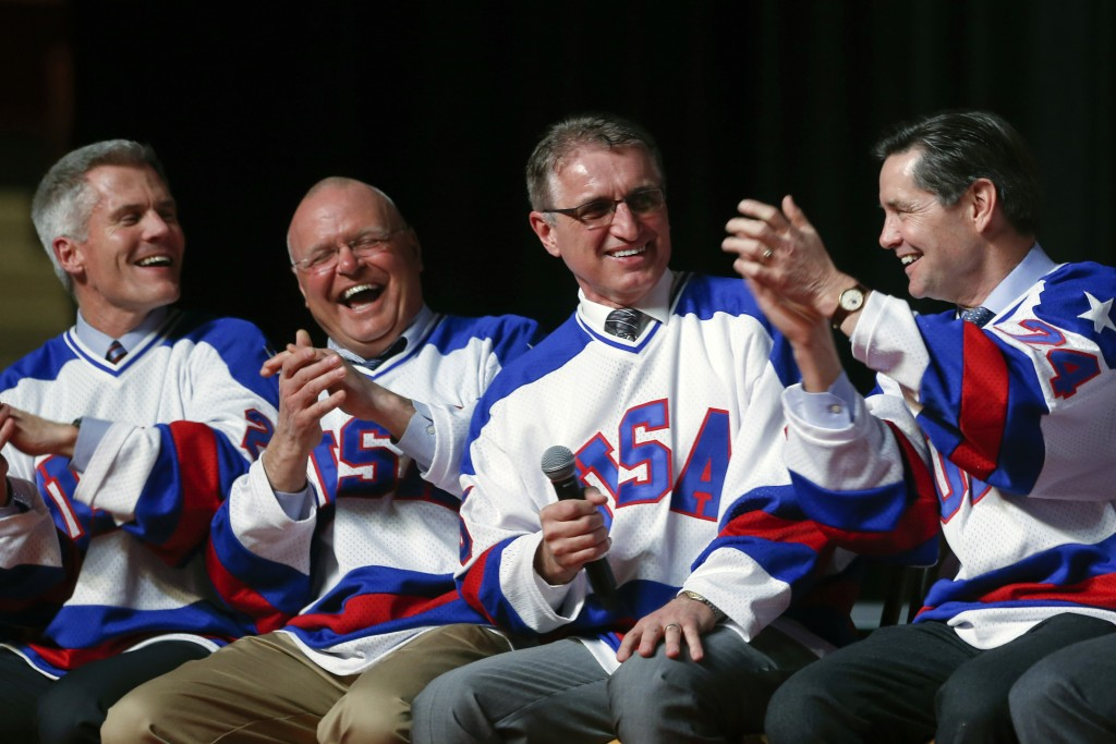 """FILE - In this Feb. 21, 2015, file photo, Buzz Schneider, second from right, of the 1980 U.S. Olympic ice hockey team, speaks during a """"Relive the Mir..."""
