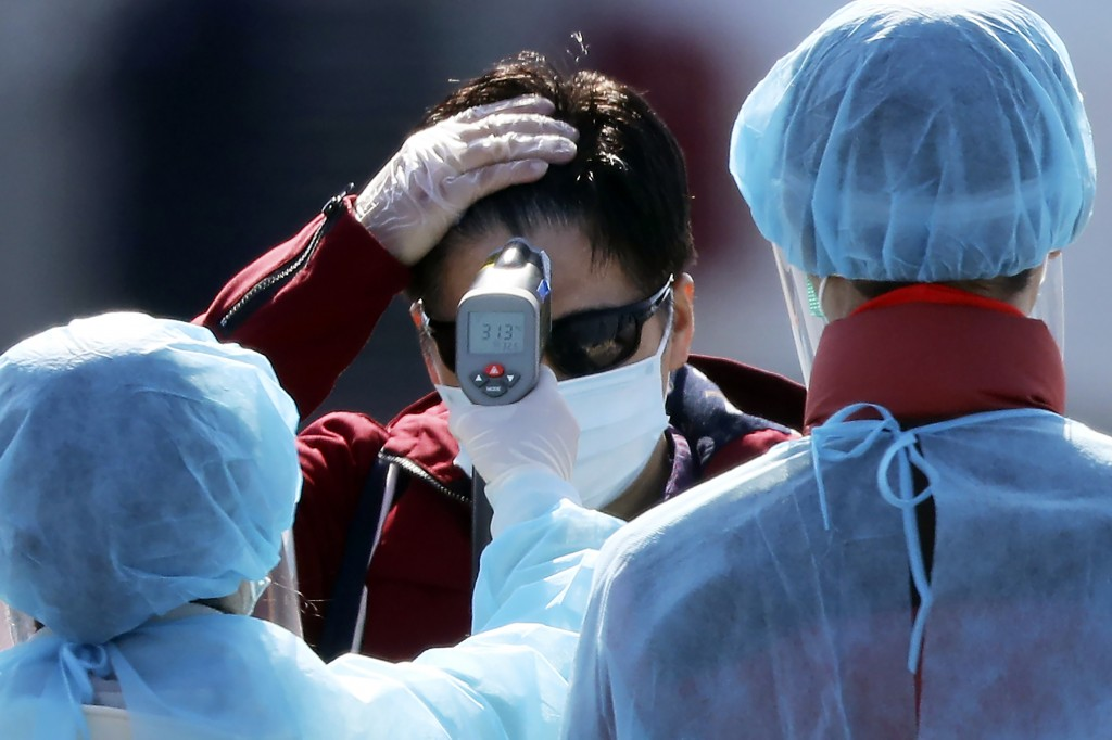 An official in protective suits measure the temperature of the foreign passengers disembarked from the quarantined Diamond Princess cruise ship before...