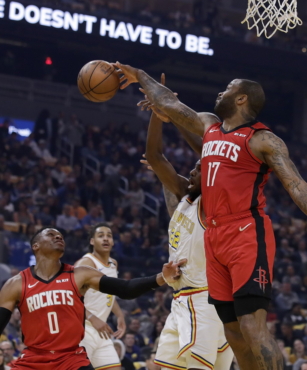 Houston Rockets' P.J. Tucker, right, rebounds over Golden State Warriors' Andrew Wiggins (22) in the first half of an NBA basketball game Thursday, Fe...