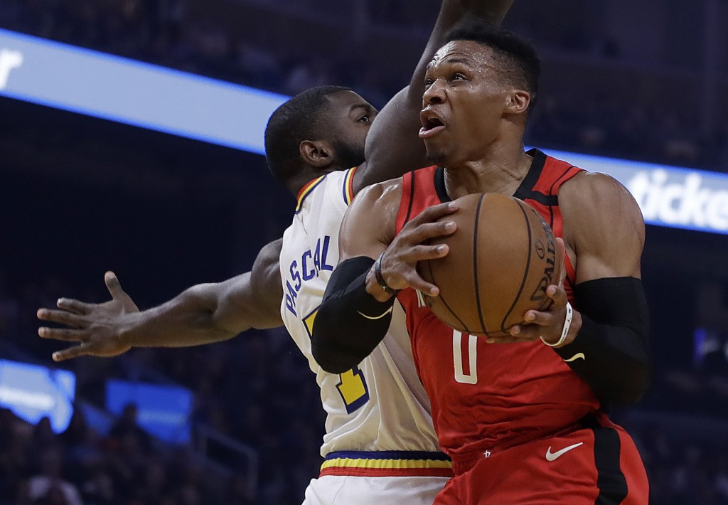 Houston Rockets' Russell Westbrook, right, looks to shoot past Golden State Warriors' Eric Paschall in the first half of an NBA basketball game Thursd...