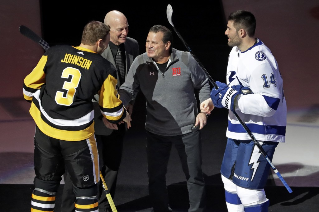 FILE - In this Feb. 11, 2020, file photo, Mike Eruzione, center right, captain of the 1980 U.S men's hockey team, and assistant coach Craig Patrick, c...
