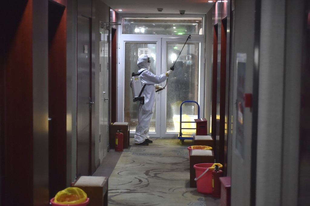 In this Feb. 21, 2020, photo released by China's Xinhua News Agency, a worker in a protective suit disintects a corridor of a hotel that has been conv...