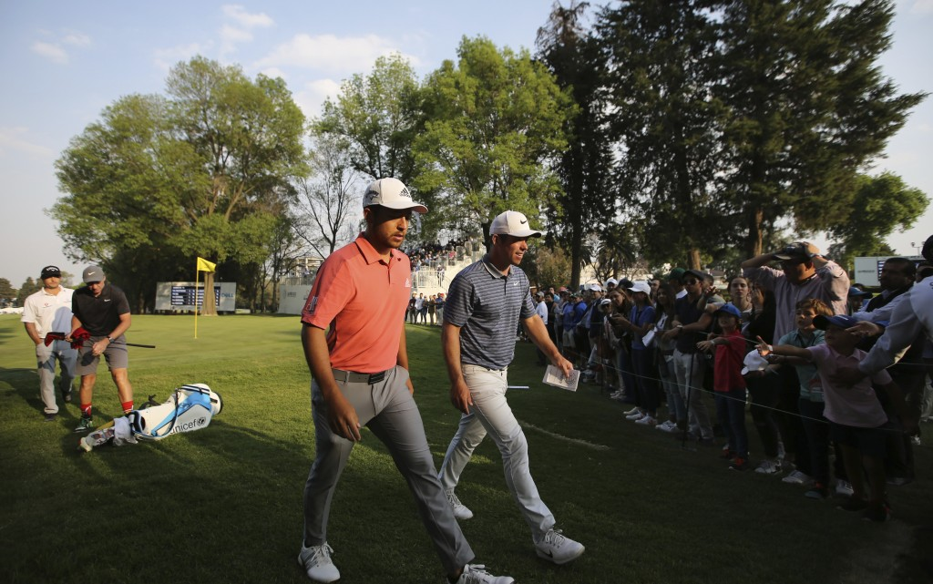 Xander Schauffele of the United States, left, and Paul Casey of England, leave the 18th green during the second round for the WGC-Mexico Championship ...