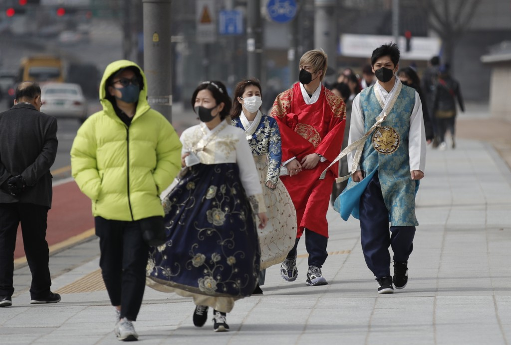 REMOVES REFERENCE TO NUMBER OF VIRAL INFECTIONS - Visitors wearing face masks walk near the Gwanghwamun, the main gate of the 14th-century Gyeongbok P...